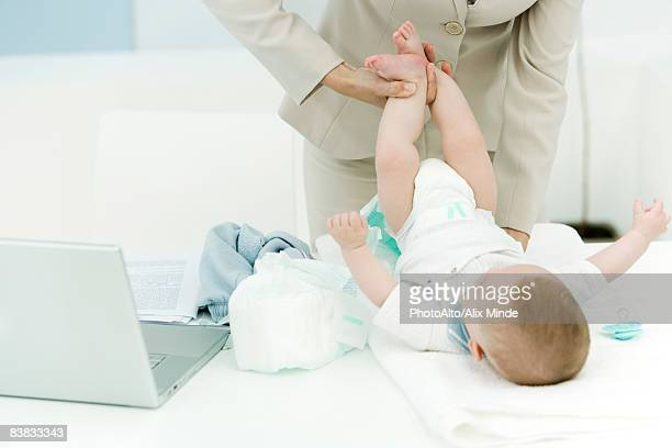 Professional woman changing baby's diaper on desk, cropped view