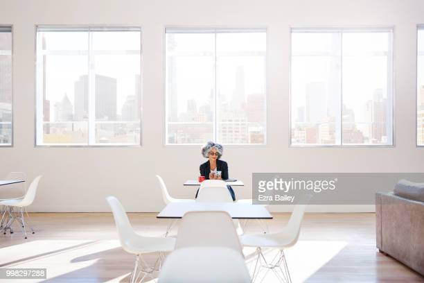 Professional woman checking emails in a clean modern open plan office.