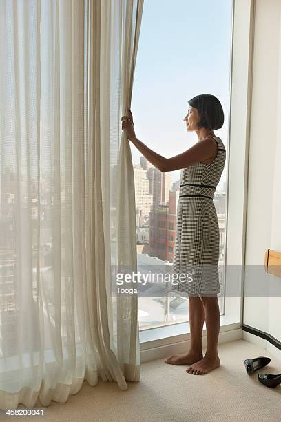 Professional woman pulling back curtain