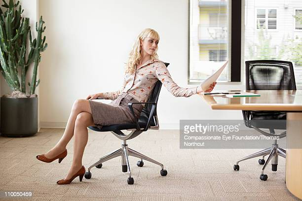 professional woman sittin at office table - high heels short skirts stock pictures, royalty-free photos & images