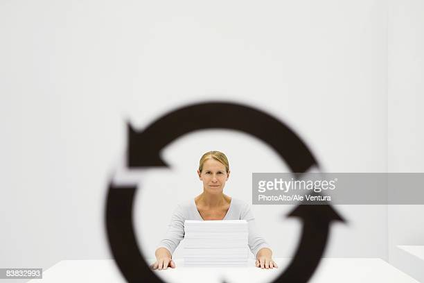 Professional woman sitting behind stack of paper, looking at camera through recycling symbol