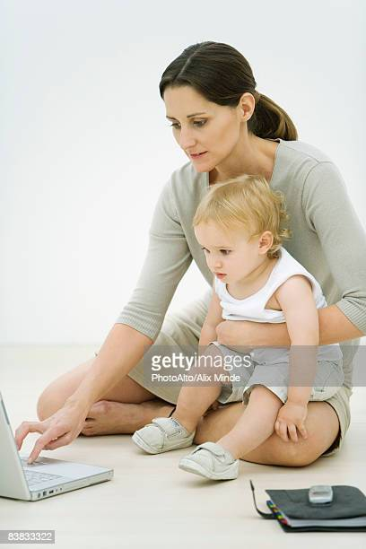 Professional woman sitting on the ground, using laptop, holding toddler on lap