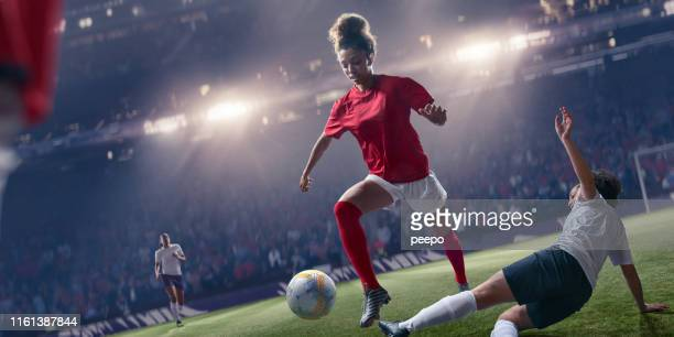 professional woman soccer player jumping over sliding tackle during match - defender soccer player stock photos and pictures