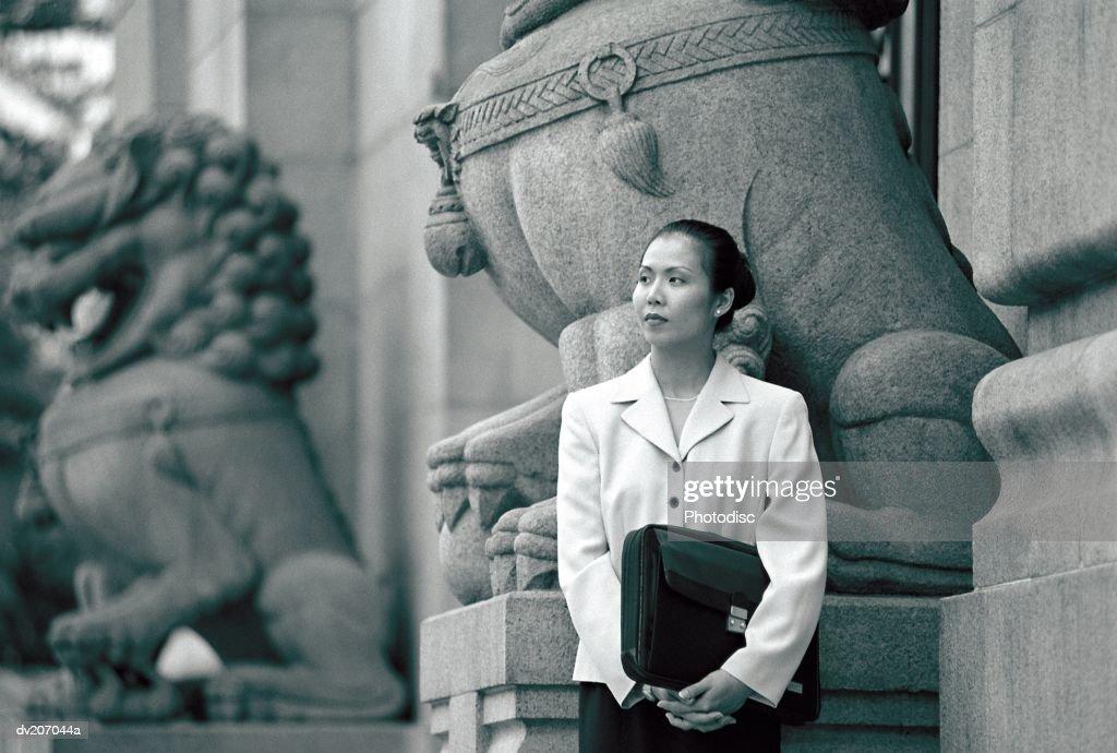 Professional woman waiting by statute : Stock Photo