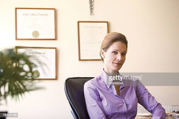 Professional woman with framed diplomas on wall behind her