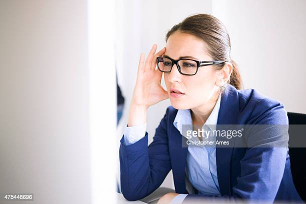 professional woman with glasses concentrating deeply on computer monitor - halfgesloten ogen stockfoto's en -beelden