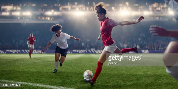 professional women soccer player about to kick ball during match - match sportivo foto e immagini stock