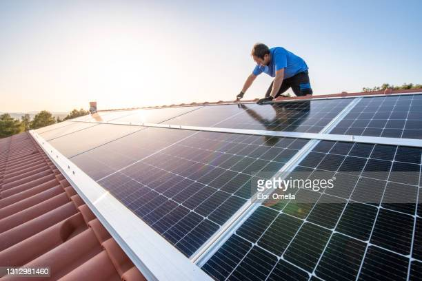 operaio professionista che installa pannelli solari sul tetto di una casa. - pannelli solari foto e immagini stock