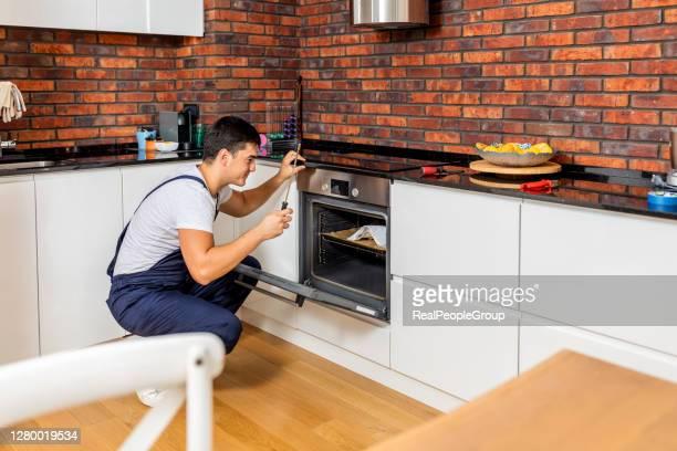 ouvrier professionnel réparant le four dans la cuisine - four people photos et images de collection