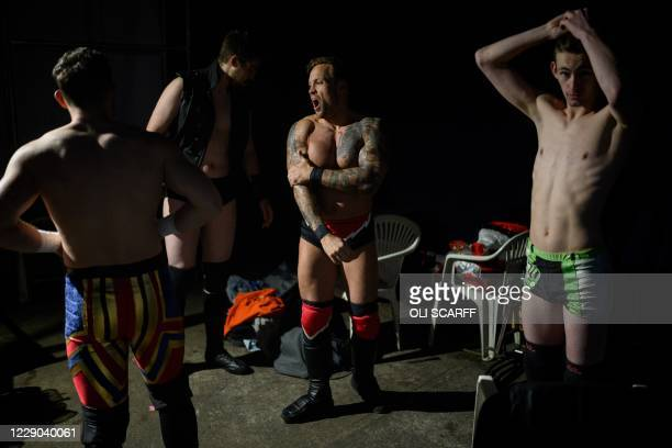 Professional wrestler Colt Miles yawns as he waits backstage before his bout during an evening of wrestling entertainment presented by promoter...