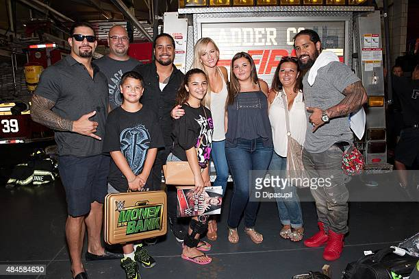 Professional wrestlers Roman Reigns Jey Uso Summer Rae and Jimmy Uso pose with members of the Amoroso family during WWE Answer The Call Tour Visits...