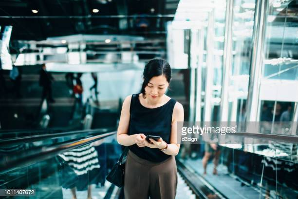professional young asian businesswoman reading emails on smartphone while riding on escalator - east asia stock pictures, royalty-free photos & images