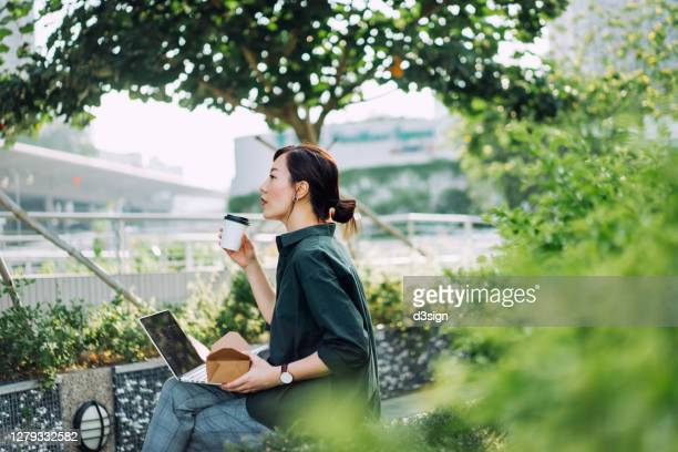 professional young asian businesswoman sitting on the bench in an urban park, working on laptop while having a healthy salad lunch box with a cup of coffee during lunch break - umweltschutz stock-fotos und bilder