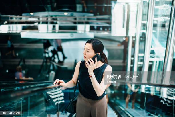 Professional young Asian businesswoman talking on smartphone while riding on escalator