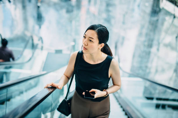 Professional young Asian businesswoman using smartphone while riding on escalator