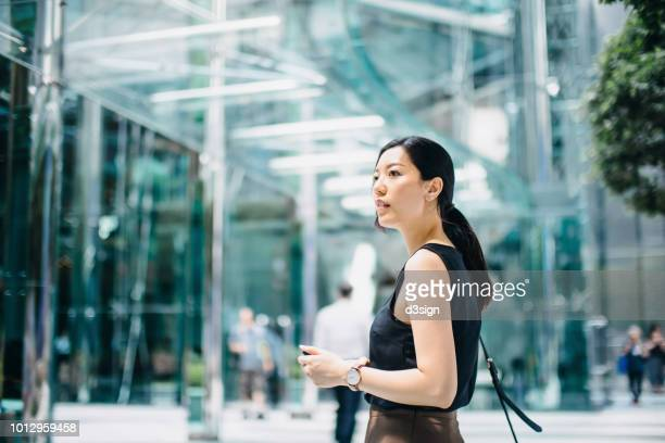professional young businesswoman standing against modern corporate building in downtown financial district - ビジネスウェア ストックフォトと画像