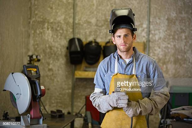 Professional young man working as welder in metal shop