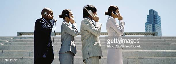 Professionally dressed men and women in line using successively more advanced phones