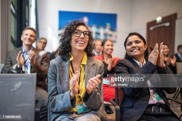 professionals applauding in a launch event - 50 59 years stock pictures, royalty-free photos & images