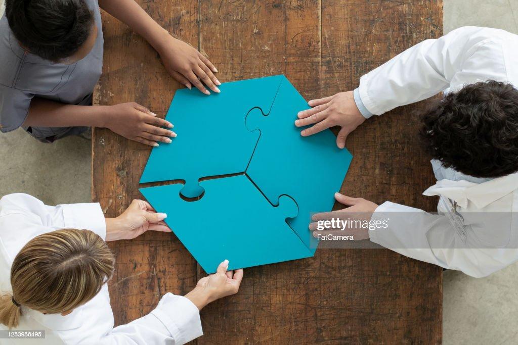 Professionals die 3 par puzzelstuk samenstellen, luchtmening : Stockfoto