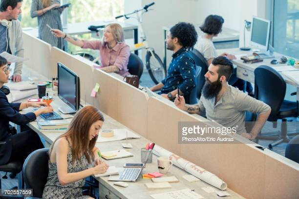 professionals coworking in shared office space - flexplekken stockfoto's en -beelden