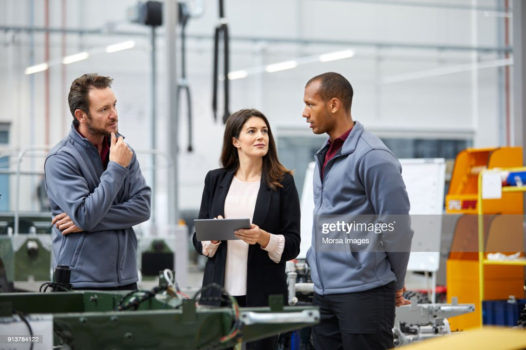 Professionals discussing in car factory : Stock Photo