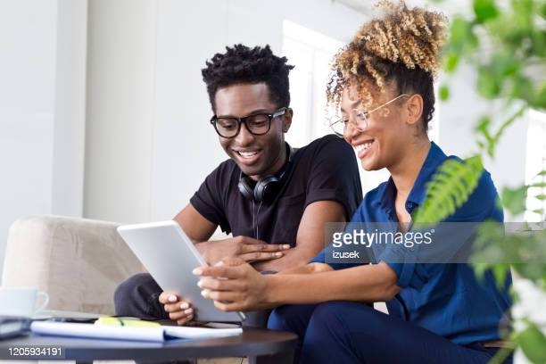 professionals discussing over digital tablet - izusek stock pictures, royalty-free photos & images