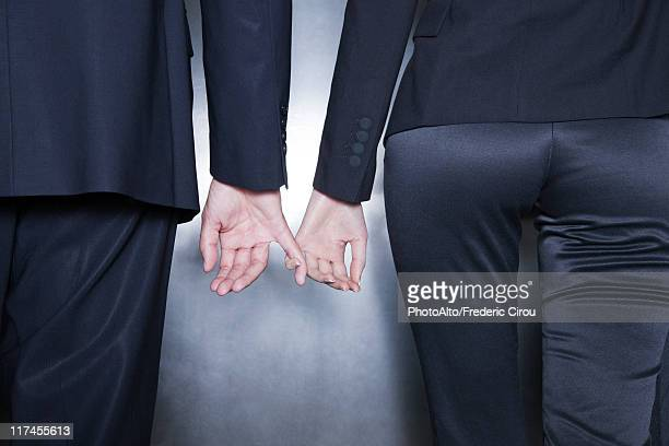 Professionals holding hands, cropped