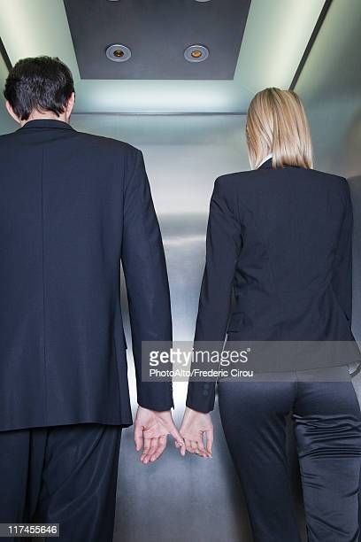 Professionals holding hands in elevator, rear view