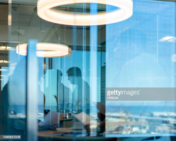 professionals in meeting seen through glass window - photographed through window stock pictures, royalty-free photos & images