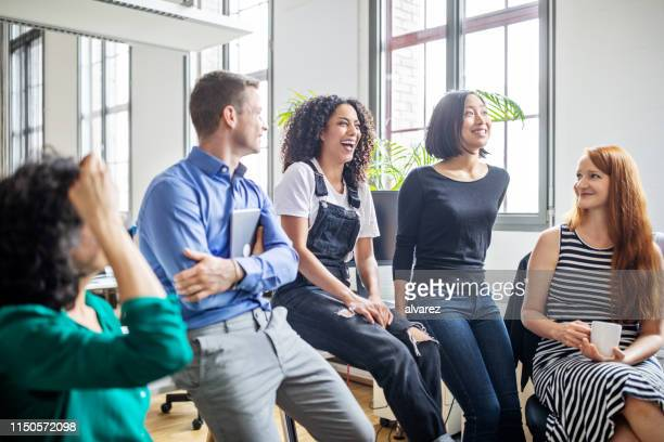 professionals laughing in a meeting - employee engagement stock pictures, royalty-free photos & images