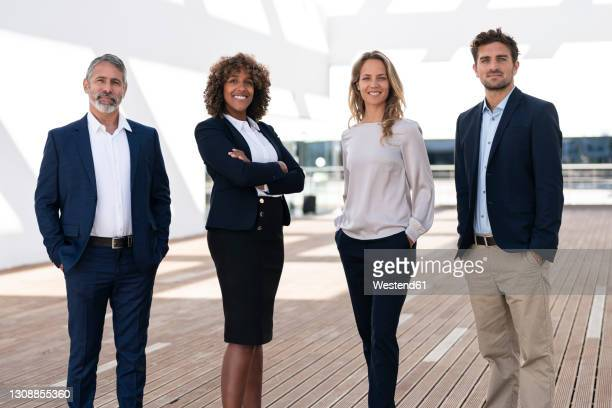 professionals smiling while standing at office building terrace - vier personen stock-fotos und bilder
