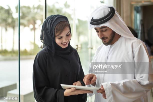 professionals using digital tablet in office - headdress stock pictures, royalty-free photos & images