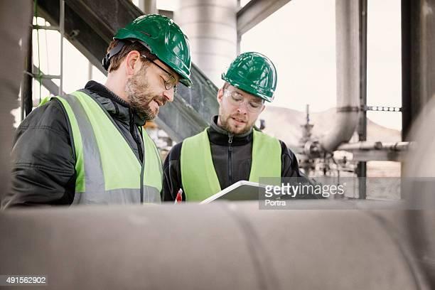 profesionales trabajando en fábrica - vertical red tube fotografías e imágenes de stock