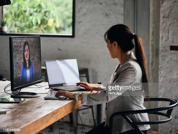 professionals working in a co-working space in taipei taiwan - video conference stock pictures, royalty-free photos & images
