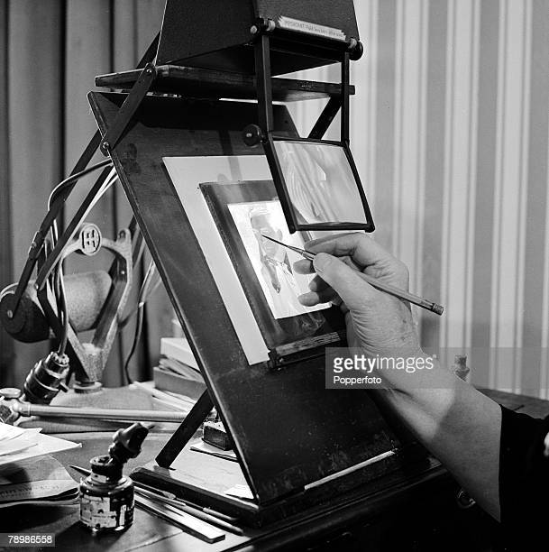 Professions England 1957 Closeup of a photographic negative being retouched by hand The operator is assisted by a magifier and strong lighting