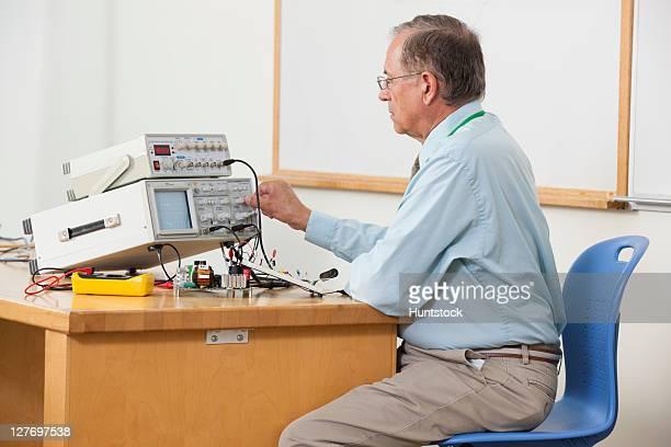 Professor adjusting oscilloscope triggering level in electronics classroom