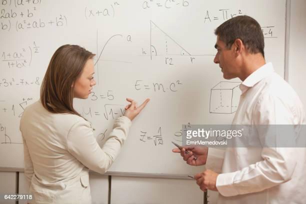 professor e aluno comunicando na frente de quadro-negro. - física - fotografias e filmes do acervo