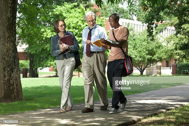 professor and students walking - college professor stock photos and pictures