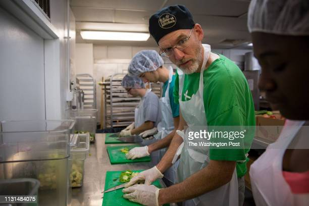 Professor Christophe Fee cuts vegetables at DC Central Kitchen with his students and other volunteers October 2014 to make meals for the homeless As...