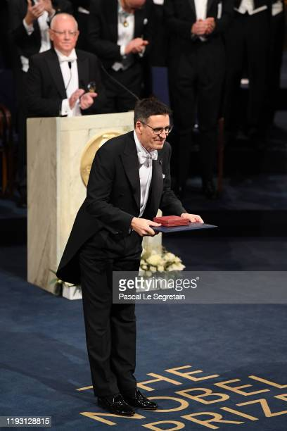 Professor Didier Queloz laureate of the Nobel Prize in Physics acknowledges applause after he received his Nobel Prize from King Carl XVI Gustaf of...