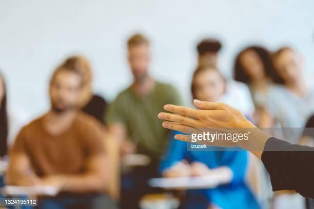 professor gesturing while teaching at university - izusek stockfoto's en -beelden