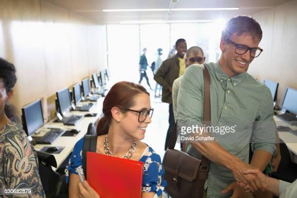 Professor greeting university students in classroom