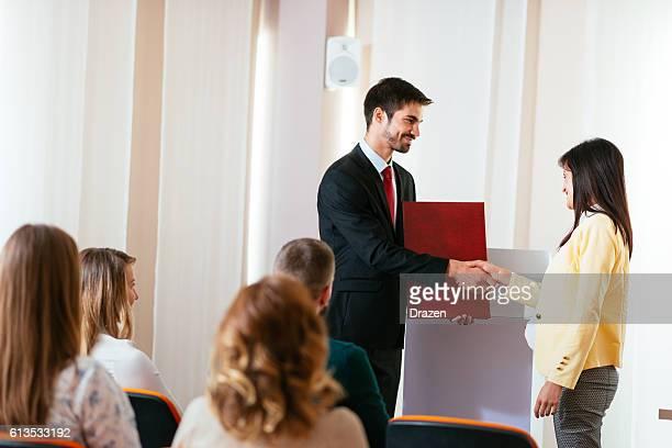 Professor hands in course certificate to student