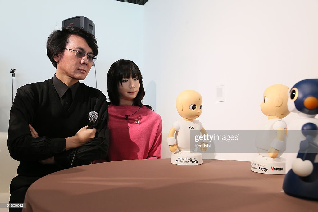 Professor Hiroshi Ishiguro talks with communication robot 'CommU' and 'Sota' during the press conference to introduce the sociable robots, 'CommU' and 'Sota' hosted by only the robot science communicator Otonaroid and the robot anchor Kodomoroid at the National Museum of Emerging Science and Technology (Miraikan) on January 20, 2015 in Tokyo, Japan. CommU and Sota, developed to improve humanoids' sense of interaction in dialogue, make people feel more engaged in conversation with them by featuring diverse eye movements and gaze directions.