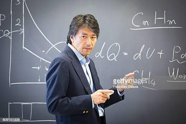 professor in front of blackboard - showing ストックフォトと画像