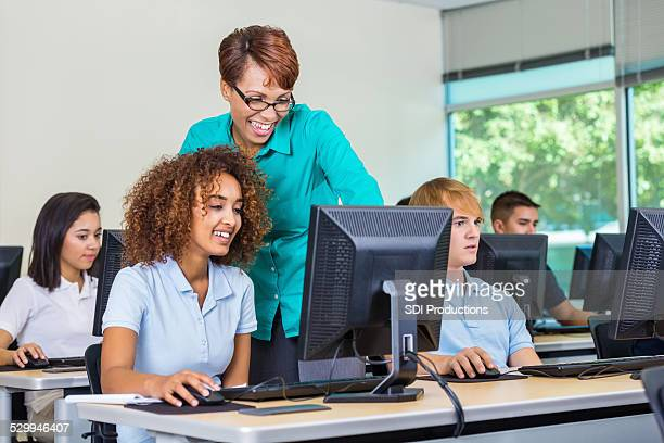 Professor in private high school computer lab teaching diverse students