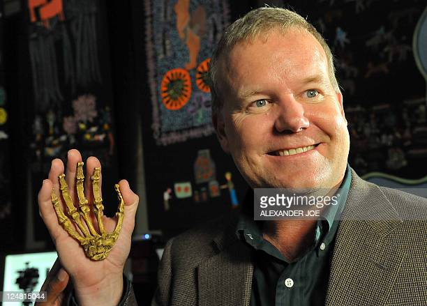 Professor Lee Berger an American who is a professor at South Africa's University of the Witwatersrand poses with the reconstructed hand of a hominin...