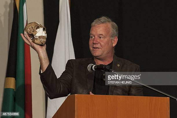 Professor Lee Berger holds up the replica of the skull of a Homo Naledi a newly discovered human ancestor during the unveiling of the discovery on...