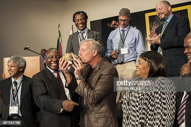 Professor Lee Berger kisses a replica of a Homo Naledi skull a newly discovered human ancestor during the unveiling of the discovery on September 10...